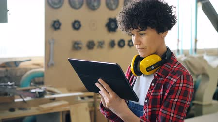 craftswoman : Female specialist working with tablet in wood workshop touching screen standing in workplace alone wearing casual clothing and protective headphones. People and devices concept. Stock Footage
