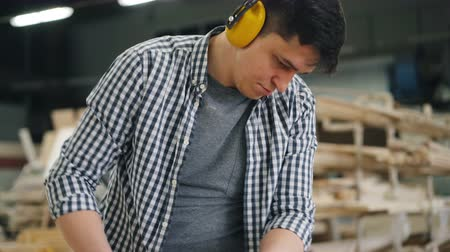 sander : Hard-working man wearing protective headphones is using belt sander machine to polish timber in workshop manufacturing woodware. People and equipment concept.