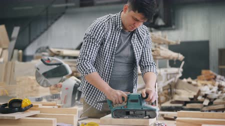 sander : Guy worker is polishing wood with belt sander working in timber workshop alone busy with woodwork. Small business, people and entrepreneurship concept. Stock Footage