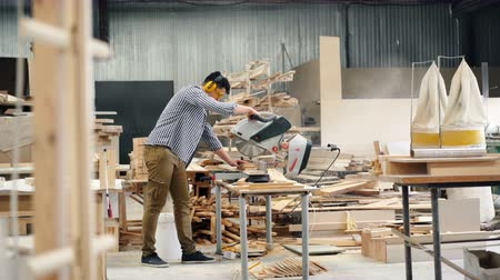 óculos de proteção : Male worker in headphones and goggles is using electric saw in wood workshop sawing timber working alone focused on activity. Business and woodwork concept.