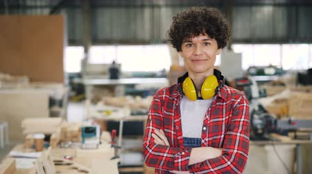 career success : Portrait of beautiful young woman carpenter standing in workroom with crossed arms looking at camera and smiling. Small business and hard-working youth concept.