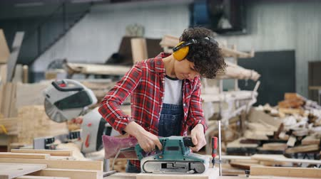 sander : Pretty girl in protective headphones is polishing wood with belt sander modern electric equipment busy in workshop. Technology, people and business concept. Stock Footage