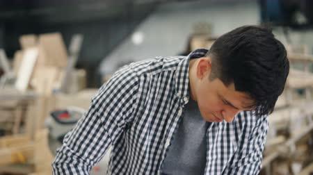 sander : Attractive guy worker is polishing timber with electric machine standing at worktable in workshop wearing casual clothes. Carpentry and equipment concept. Stock Footage