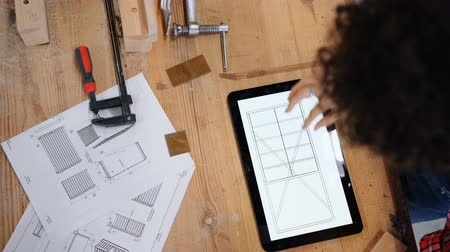 designing : Top view of female carpenter looking at technical drawings on tablet screen working in workshop alone touching gadget. People, technology and industry concept.