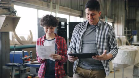 megbeszélés : Cheerful people man and woman are talking in wood workshop walking indoors with tablet and paper documents smiling discussing work. Youth and conversation concept.