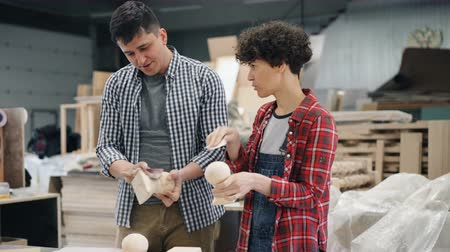 sand paper : Joyful carpenters man and woman are polishing wood with sandpaper talking and laughing in workshop. People, professional communication and job concept.