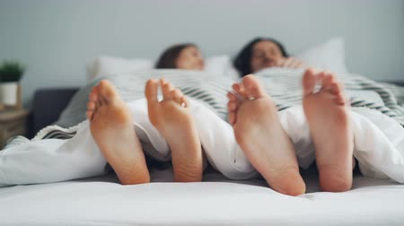 toes : Mans and womans feet are moving in bed under white blanket dancing on rhythm together, couple is having fun. Relationship, people and relaxation concept.