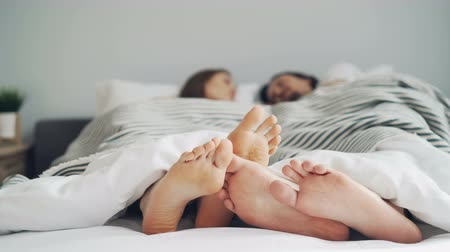 kobiece stopy : Girls and guys feet are touching in bed under blanket while people are lying together talking enjoying relationship. Youth, bedtime and family concept.