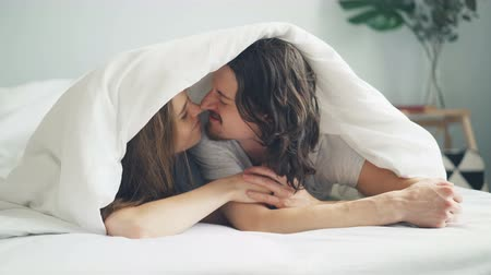meghittség : Happy couple man and woman are kissing and rubbing noses under blanket lying on bed at home together expressing love and tenderness. People and affection concept.