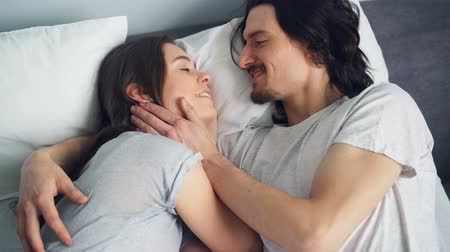 meghittség : High angle view of happy young couple talking hugging kissing in bed together lying in light bedroom enjoying married life. People, love and lifestyle concept. Stock mozgókép