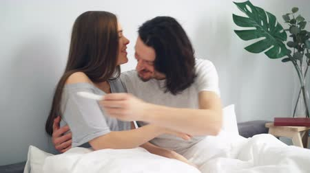 cercasi : Pregnant girl is giving guy pregnancy test, happy couple is kissing hugging sitting in bed at home together. Modern lifestyle, family and emotions concept. Filmati Stock
