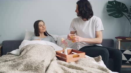 homely : Loving husband handsome bearded guy is bringing breakfast on tray for sleeping wife in bedroom, girl is waking up kissing man and drinking fruit juice.