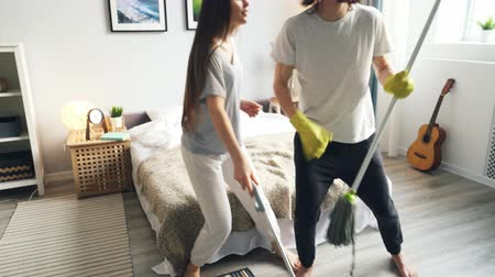 mopping : Cheerful young people are doing housework and having fun with mop and vacuum cleaner pretending to play guitar singing. Music, lifestyle and family concept.