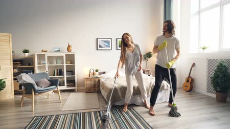 mopping : Girl and guy are doing housework and having fun with vacuum cleaner and mop singing dancing enjoying activity. Joyful youth, lifestyle and family concept.