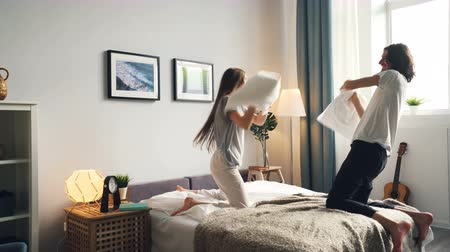 descuidado : Girlfriend and boyfriend attractive young people are fighting pillows having fun then kissing in bed at home. Modern lifestyle, youth and entertainment concept.