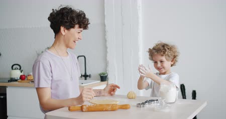 travieso : Happy child is having fun with flour clapping hands cooking pastry with mom sitting at table in kitchen at home. Joyful childhood, food and people concept.