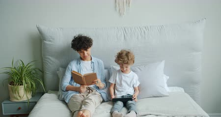 irodalom : Young lady mother is reading book while small son is enjoying tablet sitting in bed at home holding modern device. People, gadgets and literature concept. Stock mozgókép