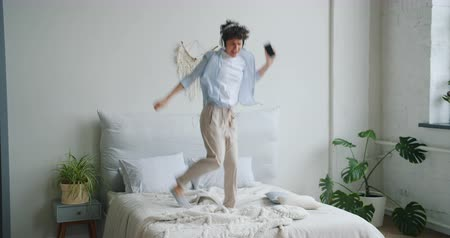 çılgın : Cute active girl is jumping dancing on bed wearing headphones holding smartphone in hand enjoying leisure time alone in house. Lifestyle and millennials concept. Stok Video