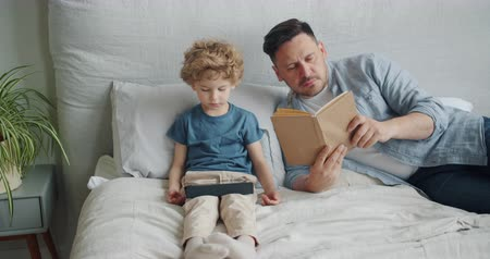 мультфильмы : Serious guy is reading book in bed while small child son is watching cartoons on tablet in bedroom. Modern lifestyle, fatherhood and childhood concept. Стоковые видеозаписи