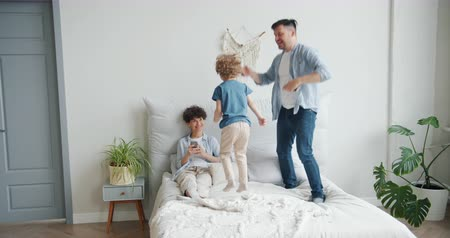 заботливый : Father and son are jumping on bed at home while young cheerful mother is using smartphone smiling having fun. People, family and modern lifestyle concept.