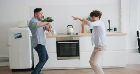 buta : Joyful couple man and woman are dancing at home in kitchen having fun together moving hands and bodies. Modern lifestyle, music and happiness concept.