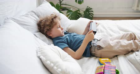 karikatury : Small child boy with blond curly hair is watching cartoons using tablet lying in bed alone relaxing at home enjoying modern technology. Children and gadgets concept.