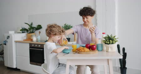 ailelerin : Slow motion of young mother putting cereal on plate for small son in kitchen at home sitting at table together enjoying breakfast. People and family concept.