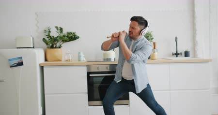 imaginární : Silly man in headphones is singing in spoon in kitchen dancing playing imaginary guitar having fun alone in apartment. People and modern lifestyle concept. Dostupné videozáznamy