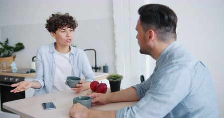 divorce : Unhappy couple man and woman are agruing sitting at table in kitchen talking with angry faces discussing marital problems. People, relationship and emotions concept.