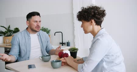 zařvat : Slow motion of angry man yelling at unhappy wife sitting in kitchen at table fighting discussing problems. Relationship, unhappiness and apartment concept.