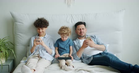 hmota : Slow motion of mother and father young people using modern smartphones while child small boy is holding tablet in bed. Gadget addiction and technology concept. Dostupné videozáznamy