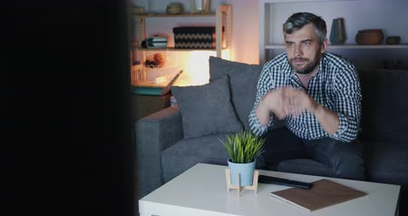 watching news : Serious bearded man is watching TV at night in dark apartment sitting on sofa concentrated on television program. People, house and modern technology concept. Stock Footage