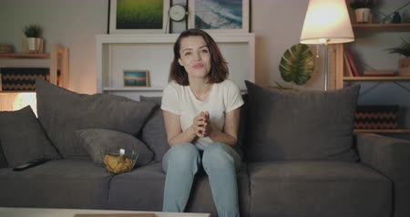 комедия : Happy young lady is watching TV at night laughing having fun sitting on sofa alone enjoying modern television. Emotions, entertainment and lifestyle concept.