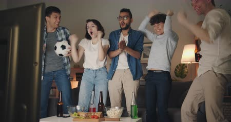 amico : Cheerful sports fans happy young people are watching football on TV cheering doing high-five and hugging at night at home. Friendship and entertainment concept. Filmati Stock