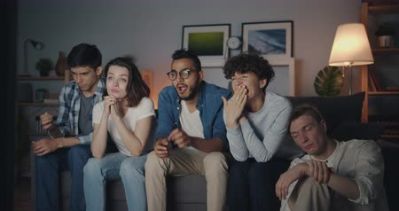 domácké : Multiracial group of young people is watching TV at home at night yawning sitting on couch together with sleepy faces. Friendship and leisure time concept.