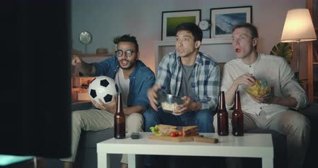 podporující : Emotional young guys students are watching soccer game on TV eating snacks celebrating victory sitting at home at night together. Youth and fun concept. Dostupné videozáznamy