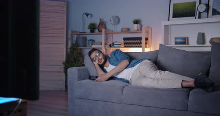 bakalář : Arabian man wearing casual clothing is sleeping on couch in front of TV relaxing at night in dark flat. Relaxation, youth lifestyle and people concept. Dostupné videozáznamy