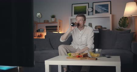 watching news : Shocked young man is watching TV breaking news drinking beer then spilling drink sitting on couch at night at home. Human reaction and television concept. Stock Footage