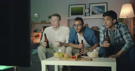 cheers : Sports fans attractive guys are watching game on TV then clinking bottles laughing celebrating victory sitting on couch in dark apartment. Youth and hobby concept. Stock Footage