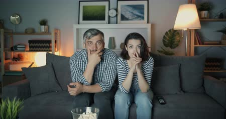 údiv : Shocked girl and guy are watching TV with serious faces touching face expressing astonishment at night sitting on sofa in apartment and looking at camera.