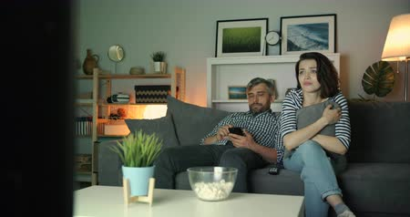 gevoelig : Sensitive woman is watching TV and crying while guy husband is using smartphone at home at night relaxing in dark apartment. People and modern technology concept.