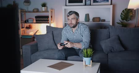 agglegény : Bearded guy is enjoying video game at home at night sitting on sofa holding joystick having fun and chewing. Pastime, lifestyle and entertainment concept.