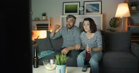 family watching tv : Husband and wife attractive young people are watching sports on TV at night cheering drinking beer hugging having fun. Entertainment and family concept.