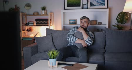 bakalář : Middle-aged bachelor is watching scary film on TV at night sitting on couch alone holding cushion expressing emotions then using remote control. People and television concept.