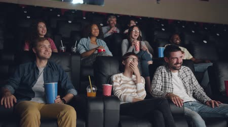 filme : Multiracial group of young people is watching movie in cinema laughing sitting on comfortable seats in dark hall. Entertainment and human emotions concept.