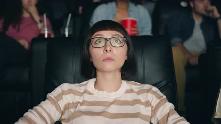 sensível : Scared young lady watching frightening thriller in cinema staring at screen with big eyes enjoying horror film. Entertainment, human emotions and students concept. Vídeos