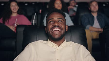 コミカル : Slow motion of cheerful African American man enjoying film in cinema laughing smiling looking at screen with joyful face. People and entertainment concept. 動画素材