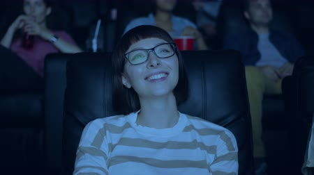 комедия : Attractive young woman in glasses is laughing smiling having fun in cinema with group of people sitting on comfy chair in dark room. Youth and emotions concept.