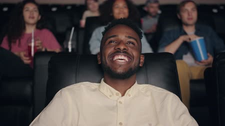 enjoyable : Happy African American man laughing in cinema watching funny comedy having fun sitting among multiethnic group of people. Youth and entertainment concept. Stock Footage
