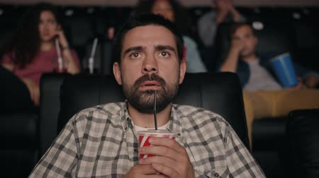 reakció : Horrified bearded guy is watching scary thriller in cinema holding drink screaming with fear looking at screen in dark room. Emotions and beverage concept.